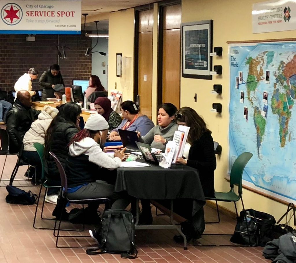People at a table - hhc outreach staff help people enroll in ACA insurance plans