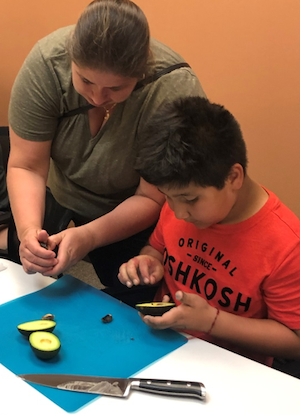 mom and son cutting avocado in cooking class
