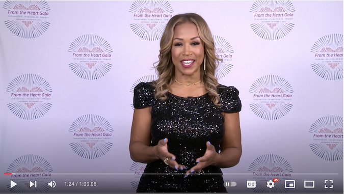 Val Warner MC host in front of HHC step and repeat backdrop